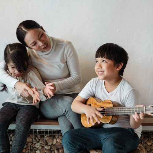 ethnic-boy-playing-ukulele-for-sibling-and-mother-in-house-4473416